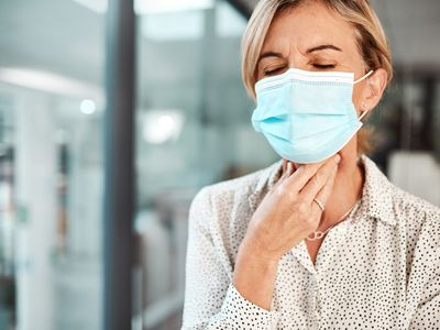 Shot of a mature businesswoman wearing a mask and rubbing her throat in an office