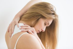 woman applying pain patch to neck and shoulder