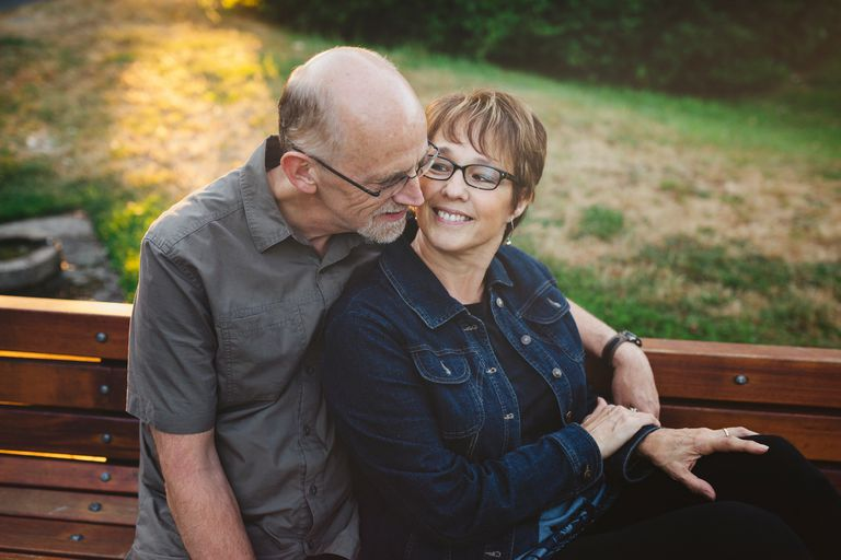 Couple hugging on park bench.