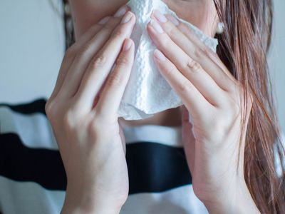 A woman blowing her nose