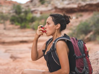 A hiker with asthma using her inhaler