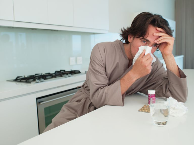 Man with a cold blowing his nose in a kitchen