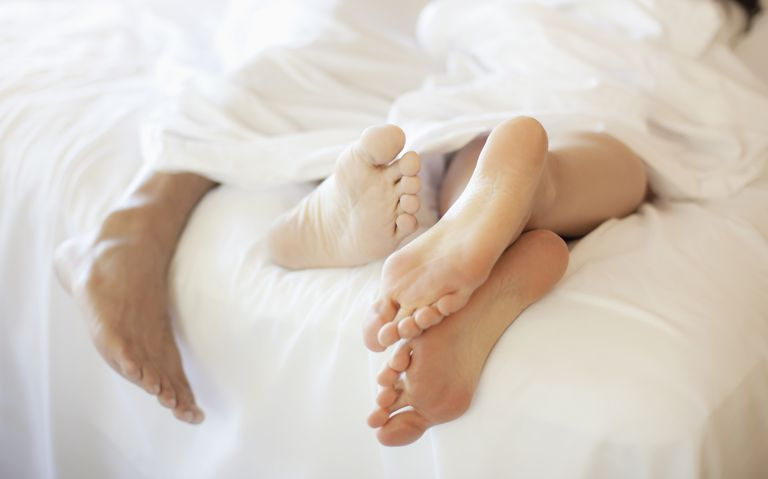 Couple's feet hanging of the end of a bed