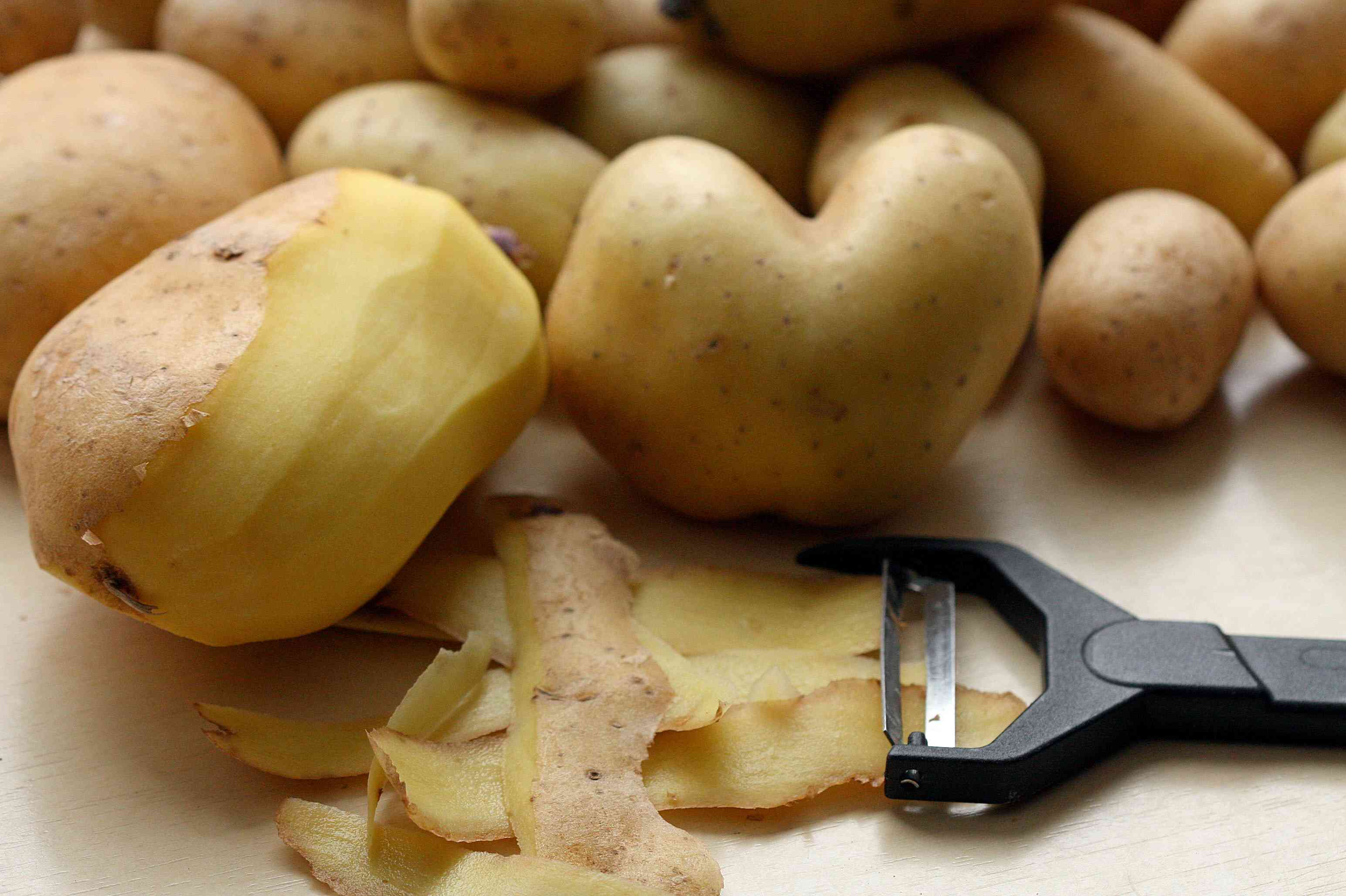 A pile of potatoes, one partially peeled, next to a peeler.