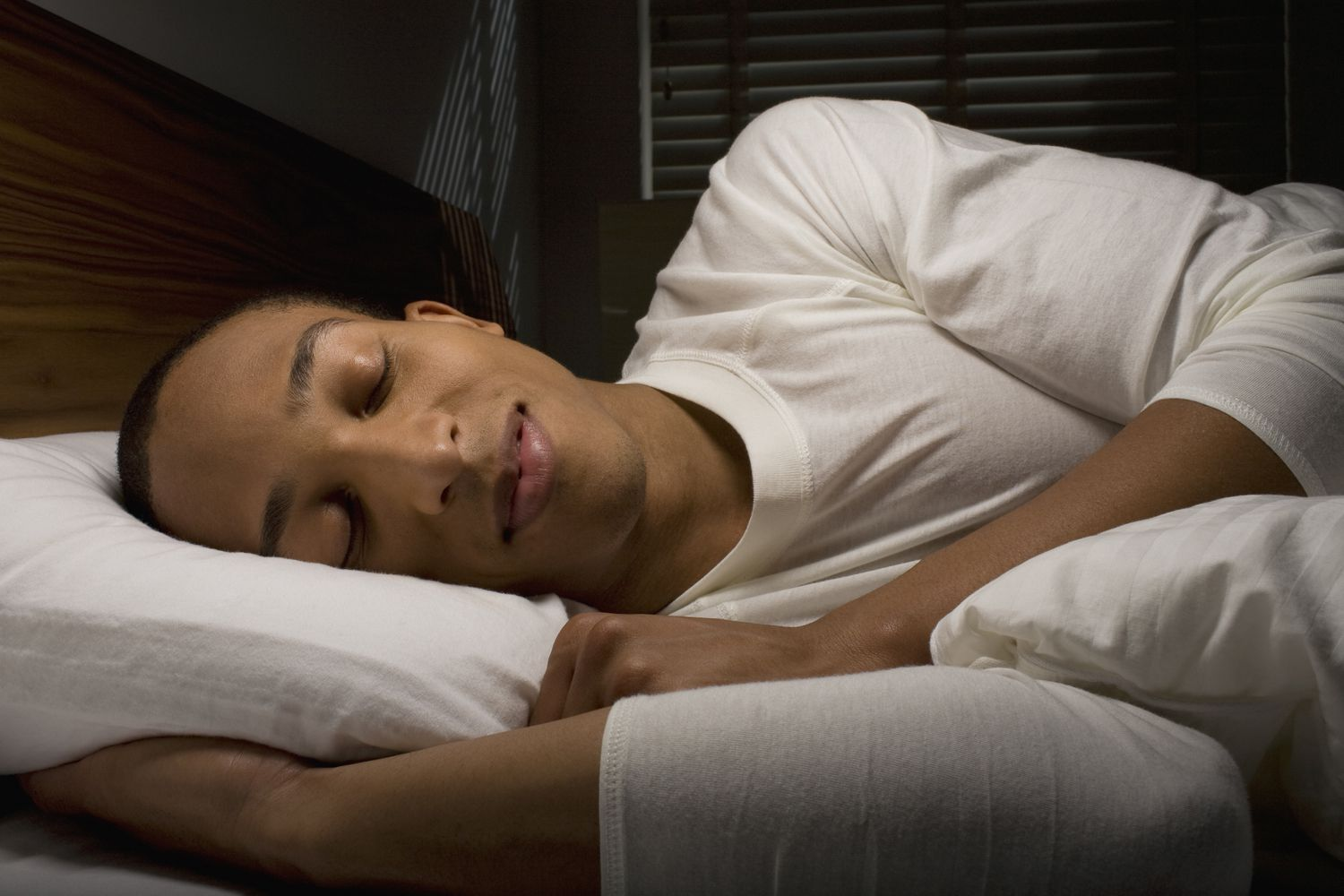 A person sleeping in bed while smiling
