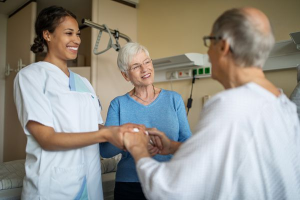 Caring nurse holding hand on a senior male patient - stock photo
