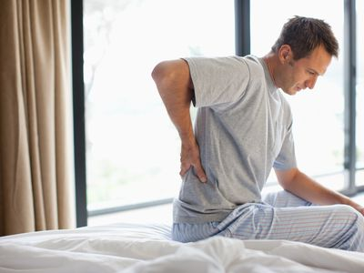 Man with back pain sitting on the edge of the bed