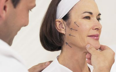Doctor examining a woman's face marked for a facelift - stock photo