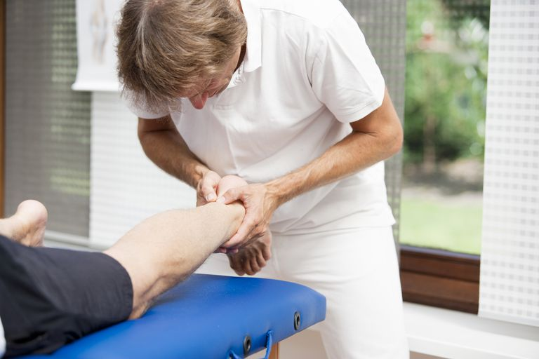Photo of a physical therapist examining a patient's Achilles tendon