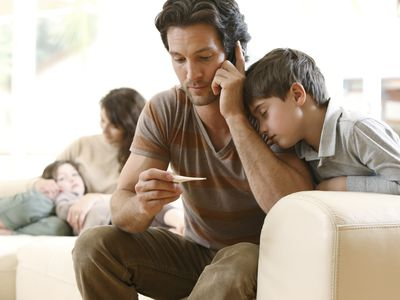 Man on the phone looking at a thermometer with his sick family in the room