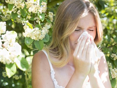 Woman Blowing Nose on Tissue Paper