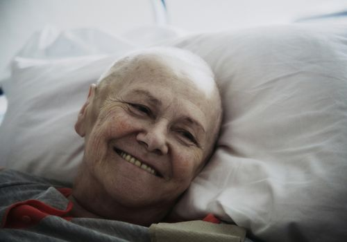 Smiling senior bald patient in hospital bed
