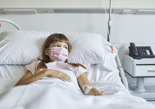Child lying in a hospital bed wearing a face mask.