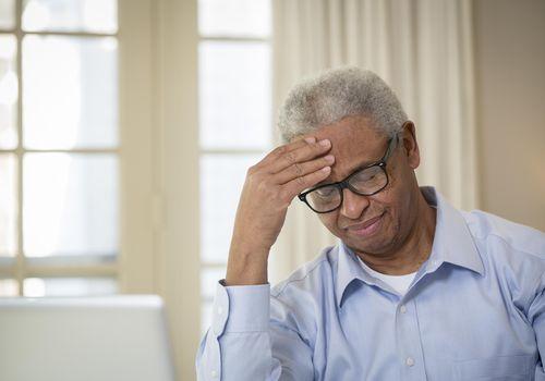 Senior African American man rubbing his forehead