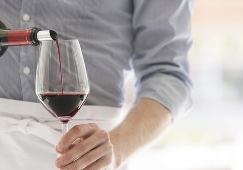 waiter pouring red wine