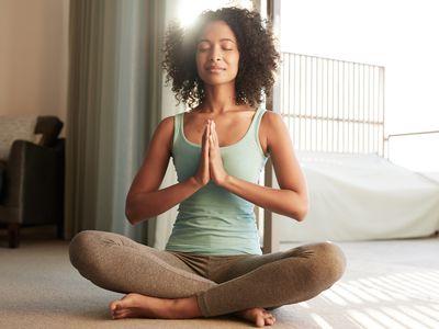 Woman sitting on the ground meditating.