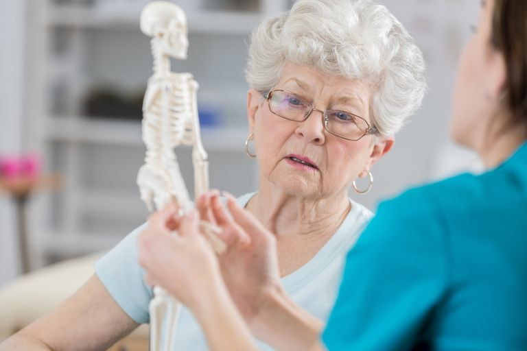 Doctor talking with senior woman and showing her something on a model skeleton