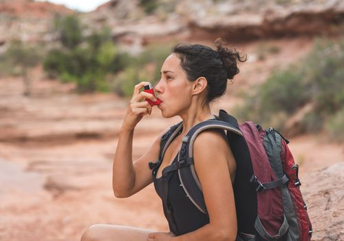 Woman using inhaler while hiking