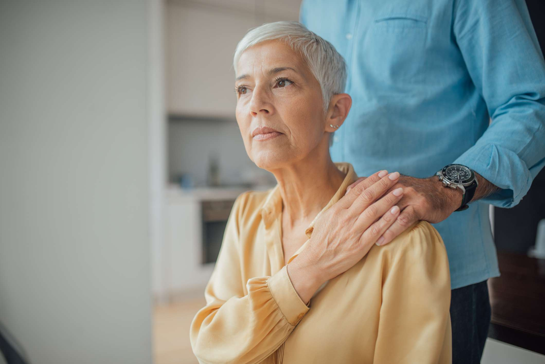 serious older woman holding partner's hand