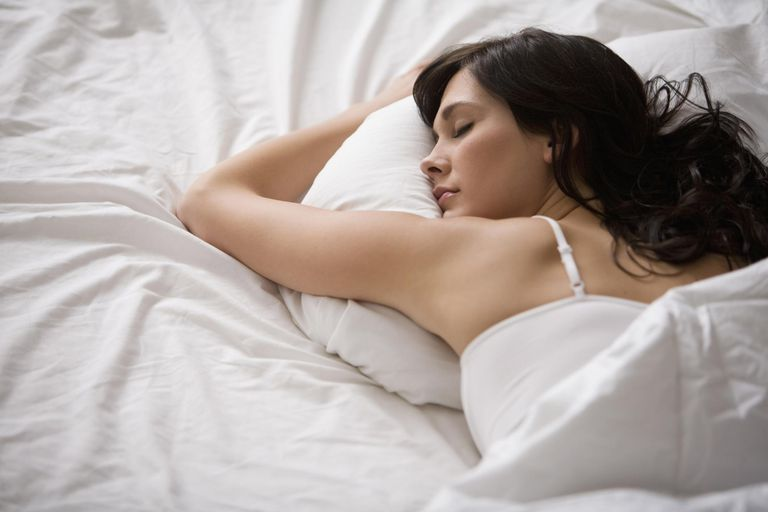 woman sleeping on her stomach holding pillow