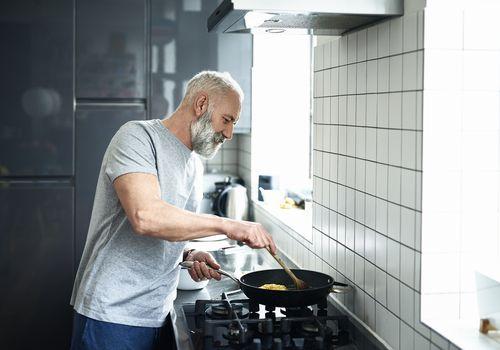 Senior man with grey beard using frying pan in modern kitchen