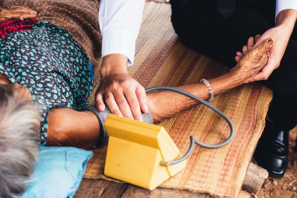 Male Doctor listening heart beat and breathing of Elderly Woman with Stethoscope with First Aid Medical Box.