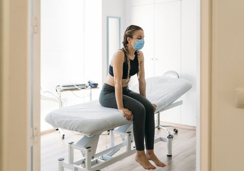 Young woman wearing a mask on an examination chair.