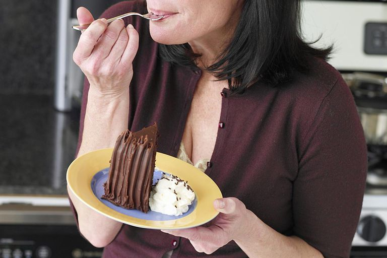 Woman eating cake, eyes closed, close-up