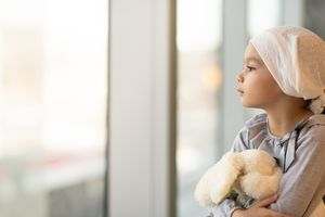 Young girl with head scarf and stuffed animal looking out a window