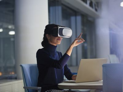 Businesswoman using virtual reality headset at laptop in office