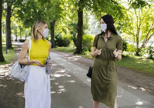 Two women walking in a park with face masks on.