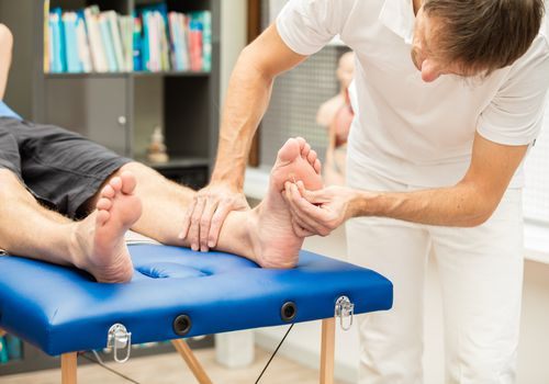 Man being poked on the bottom of his foot to examine for neuropathy or nerve pain