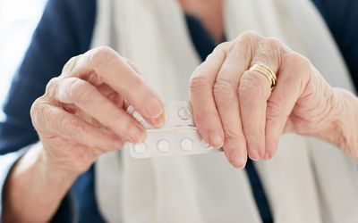 Old woman's hands trying to open medication