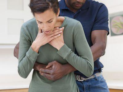 man doing heimlich maneuver on woman