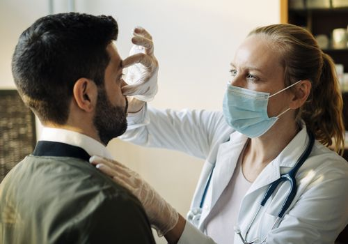 Female doctor in face mask examining male patient's eyelids