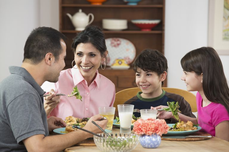 Family sits around table eating leafy greens