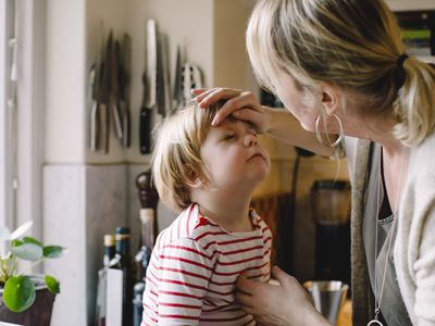 Caring mother looking at daughter's bruised eye in kitchen