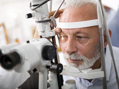 Senior man doing eye test with optometrist