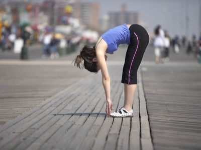 a jogger stretching and touching her toes
