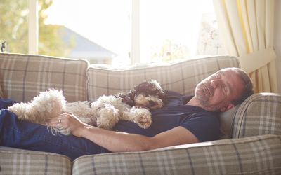 a man has a nap on the couch joined by his little dog