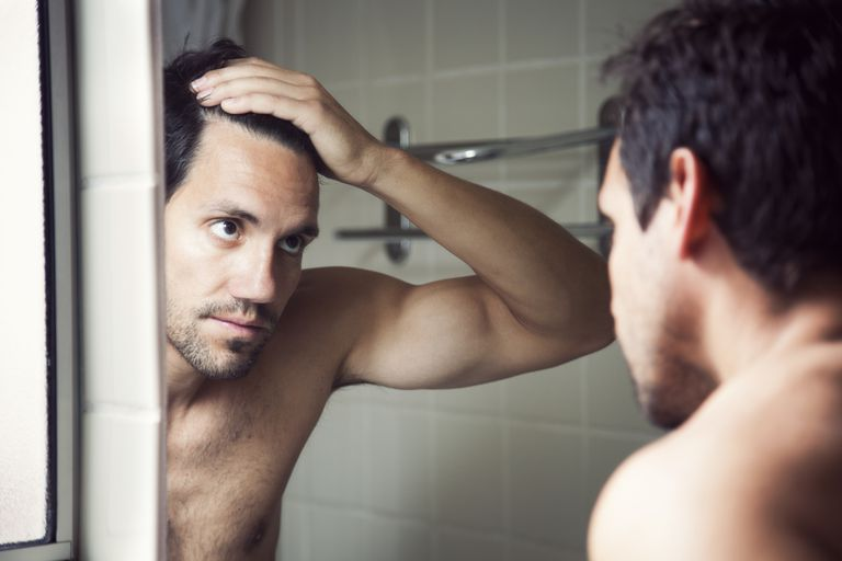 Man looking at hair loss in mirror