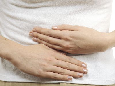 Hands on a stomach indicating suffering from stomach pain