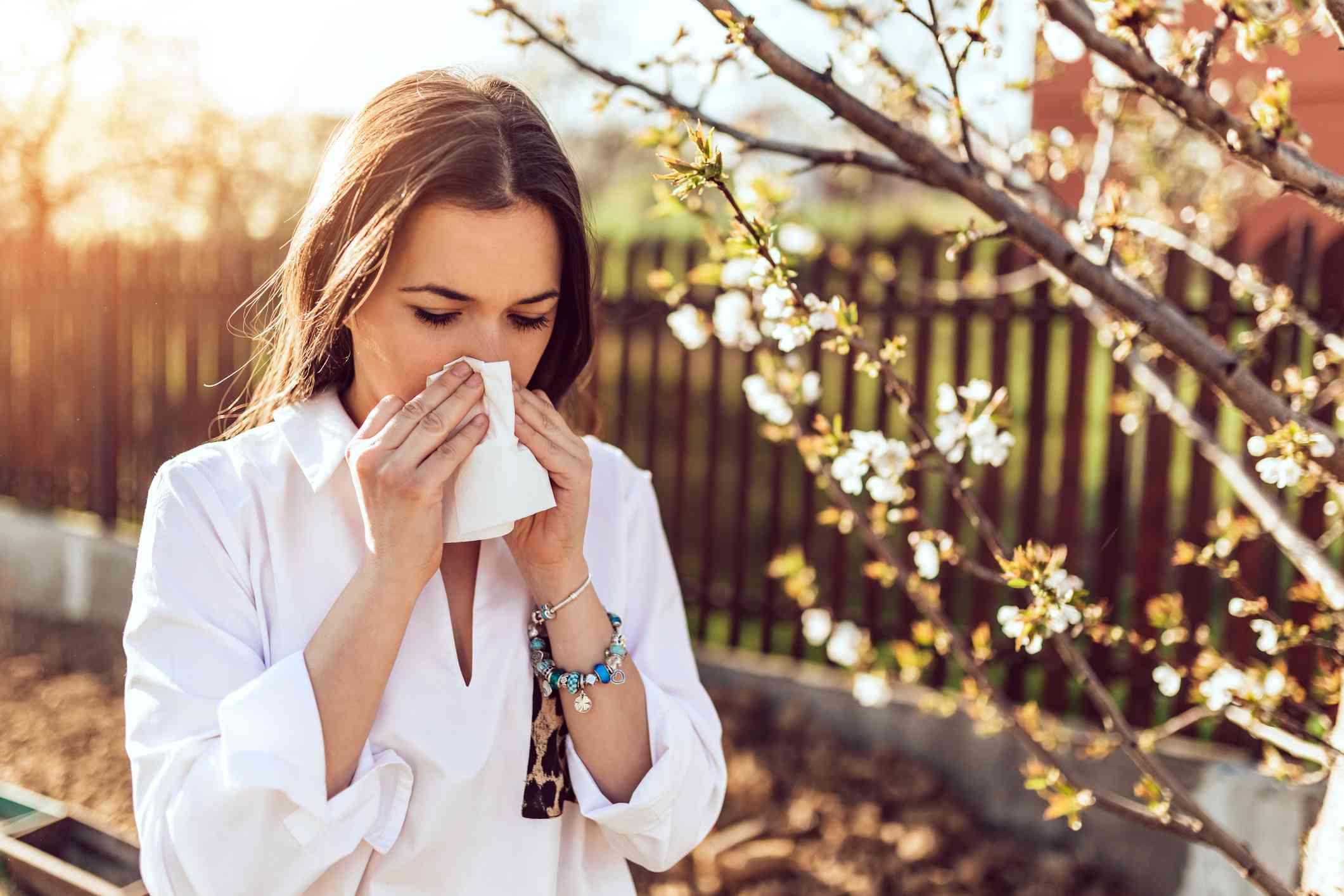 woman sneezing in the garden