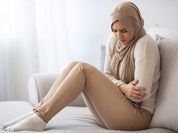 A muslim woman holding her belly in response to abdominal pain.
