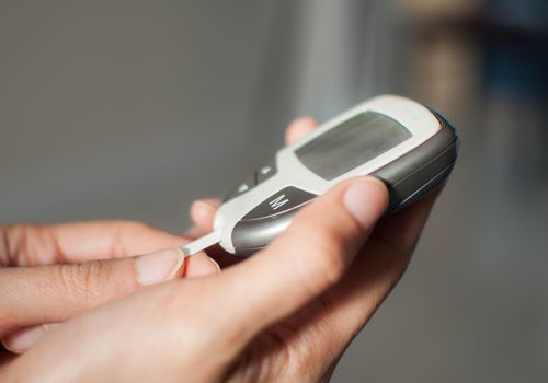 person using glucometer