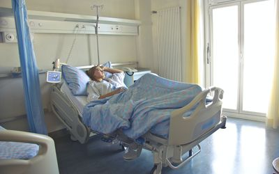 A young white woman in a hospital bed.