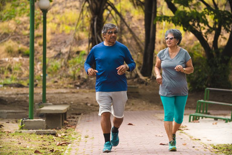 Older couple jogging in a park