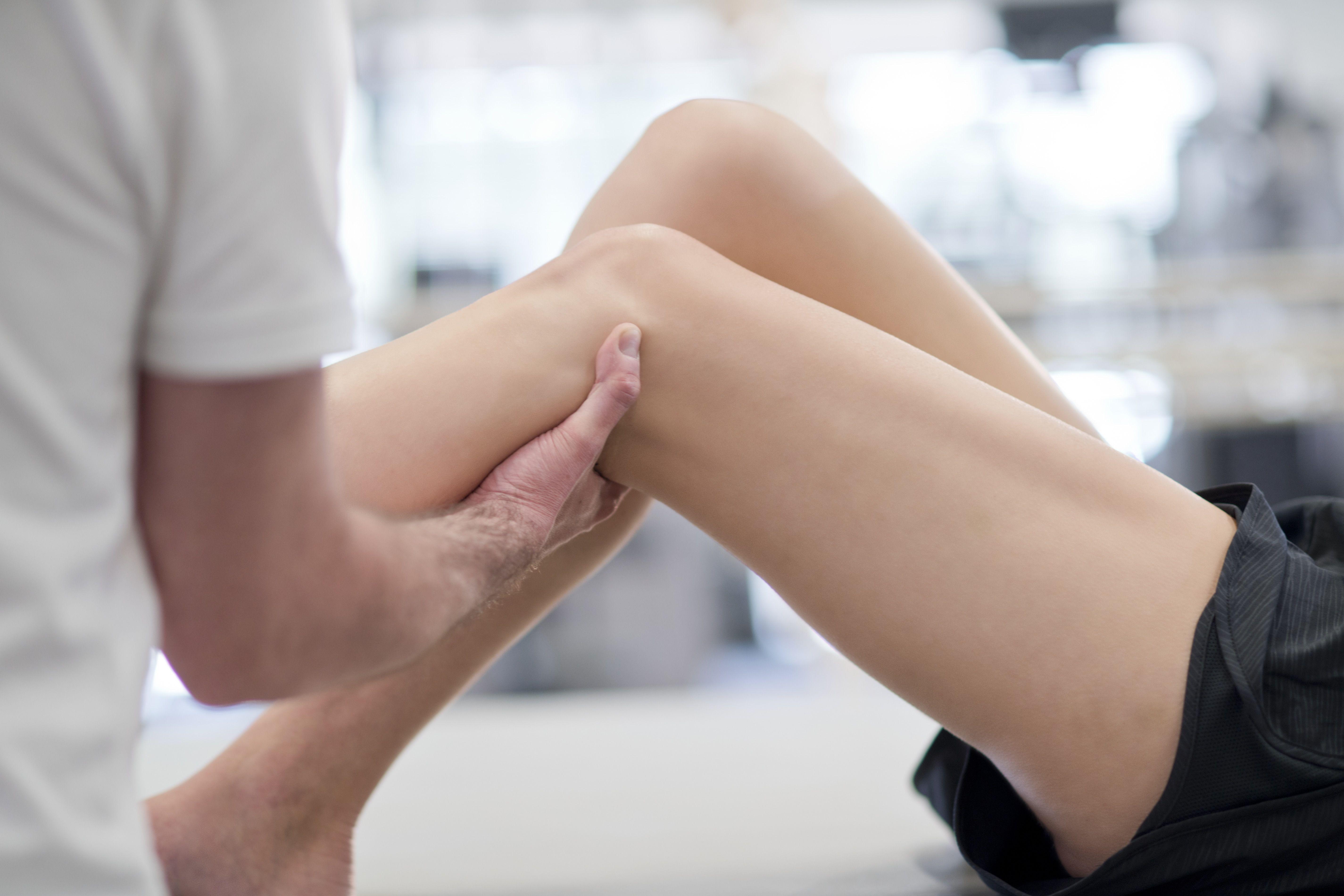 Physiotherapist massaging womans leg