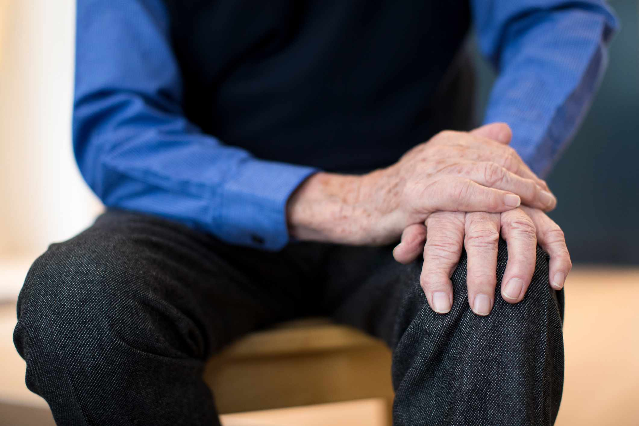 A man with Parkinson's Disease holding his knee