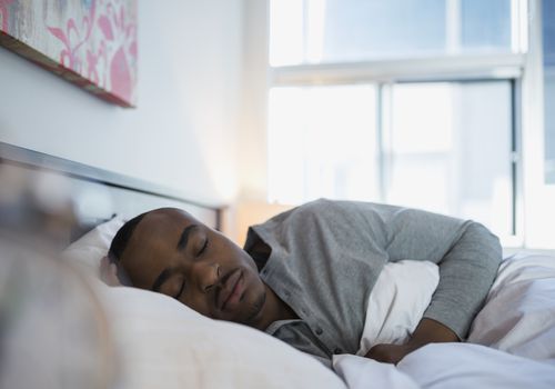 Man sleeping in bed in the morning